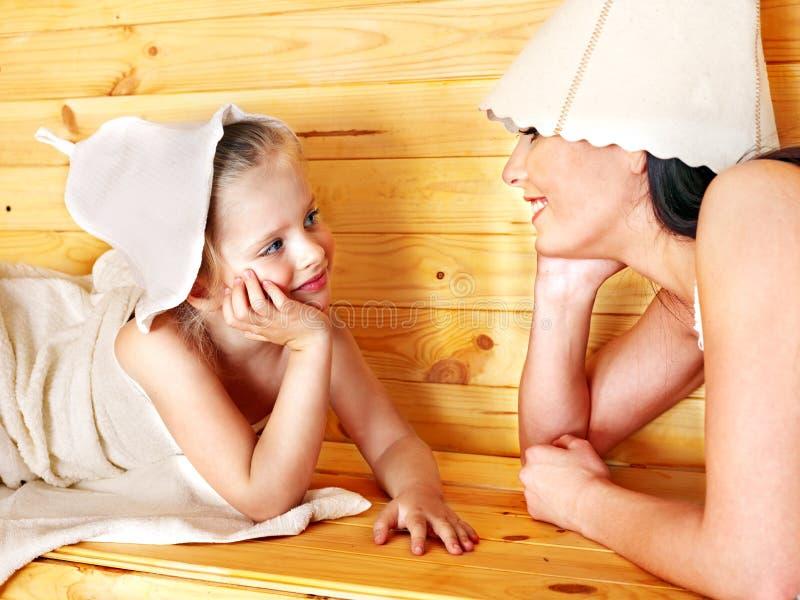 有放松在蒸汽浴的孩子的家庭。 图库摄影