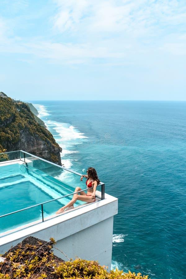 有放松在透明游泳场的黑发的妇女有意想不到的海景 库存图片