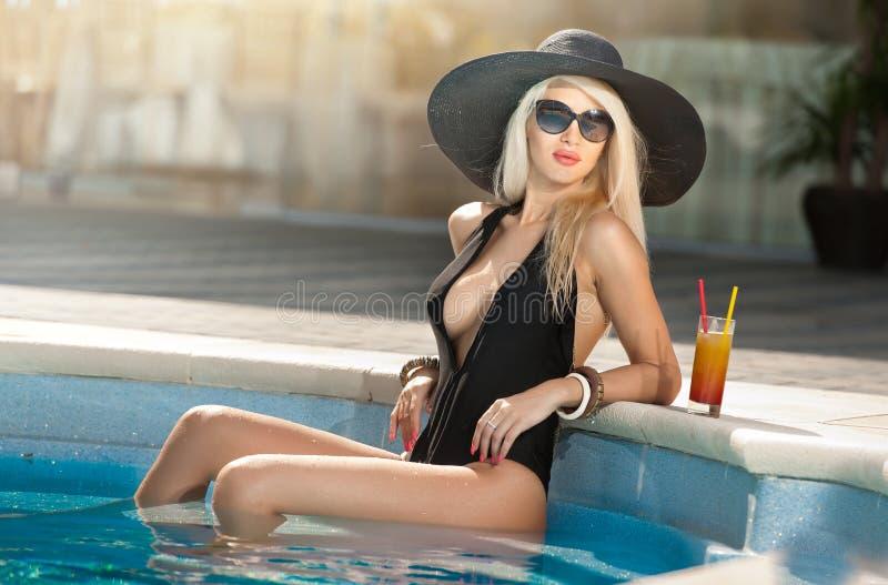 有放松在水池的太阳镜和黑小屋的美丽的肉欲的金发碧眼的女人用汁液 黑色的可爱的长的头发妇女 免版税库存照片