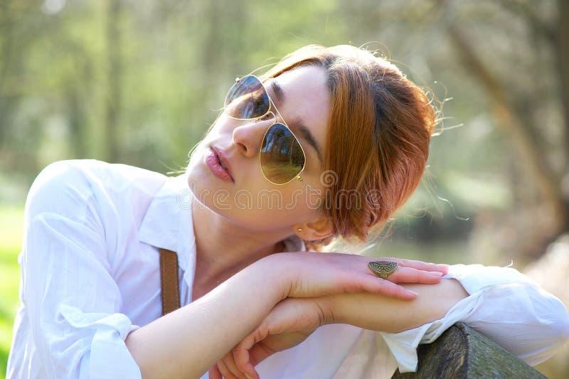 有放松的太阳镜的美丽的妇女户外 免版税库存照片