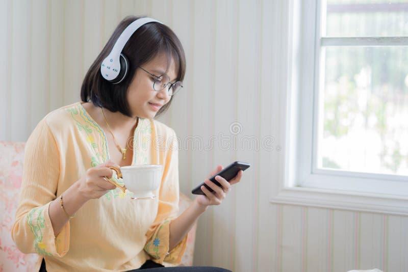 有放松的耳机和的智能手机的美女  库存照片