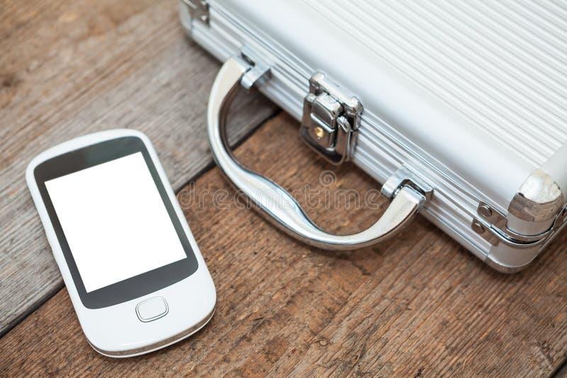 有放置在地板的手机的钢公文包 库存照片