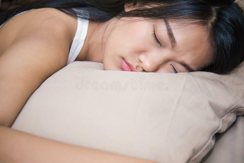 有放置在床的有吸引力的微笑的美丽的年轻亚裔妇女 免版税库存照片