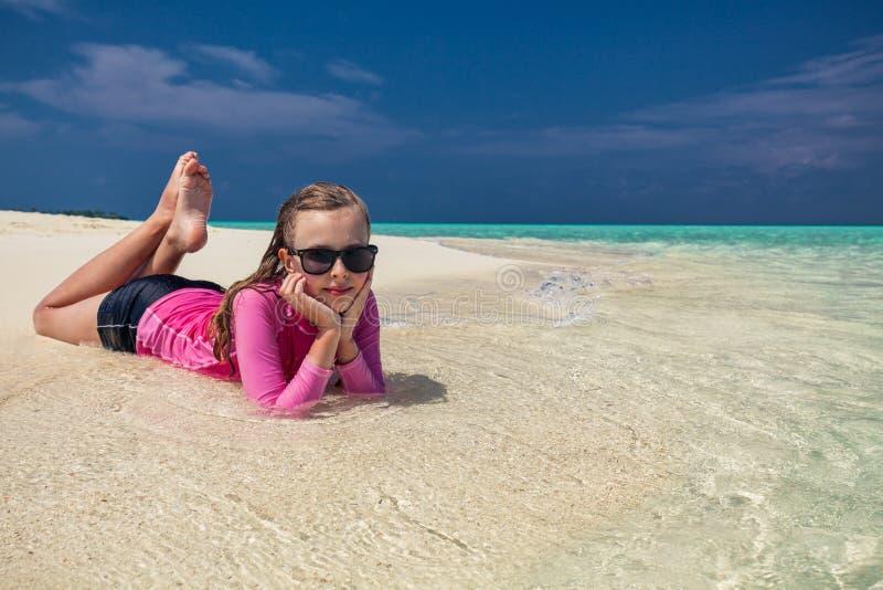 有放置在热带海滩的太阳镜的年轻微笑的女孩 免版税库存照片