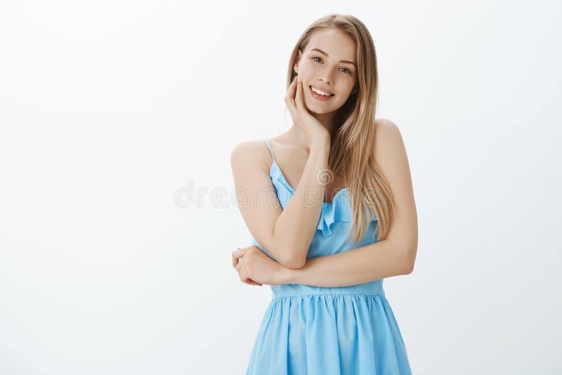 有政券头发逗人喜爱的痣的悦目有同情心和迷人的年轻女朋友在平衡接触面颊与的蓝色礼服 免版税库存图片