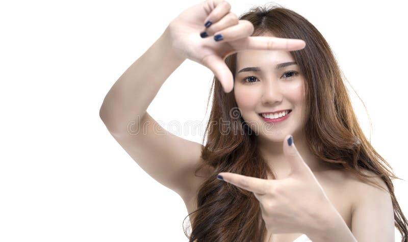 有效地做框架圆的姿态的愉快的正面年轻亚裔女孩画象在照相机 图库摄影