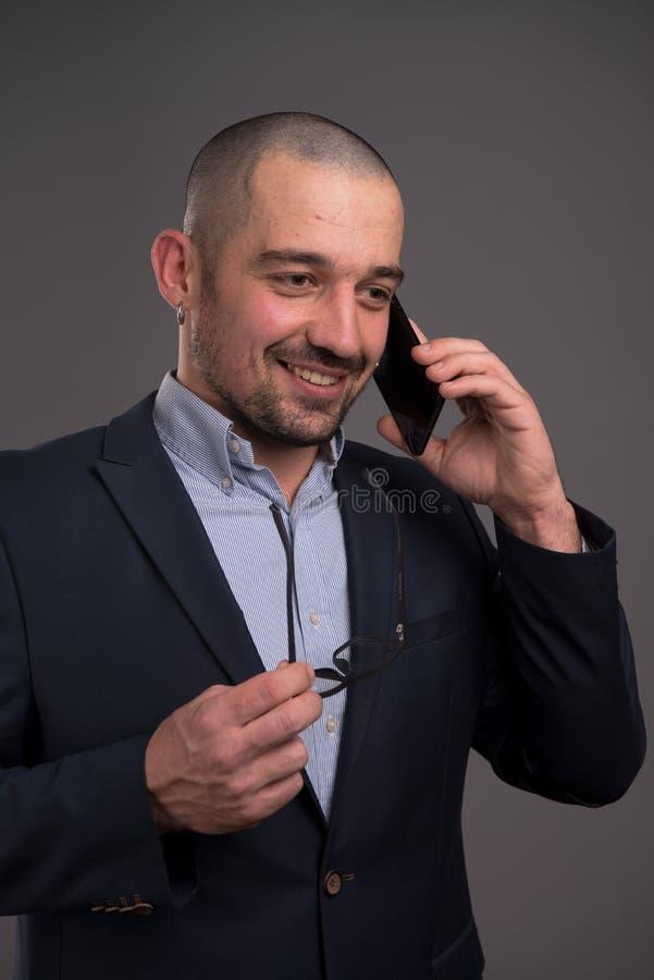 有效地谈论激动的经理在手机的业务材料 库存图片