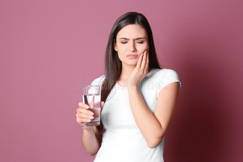 有敏感牙和杯的少妇在颜色背景的冷水 免版税库存照片