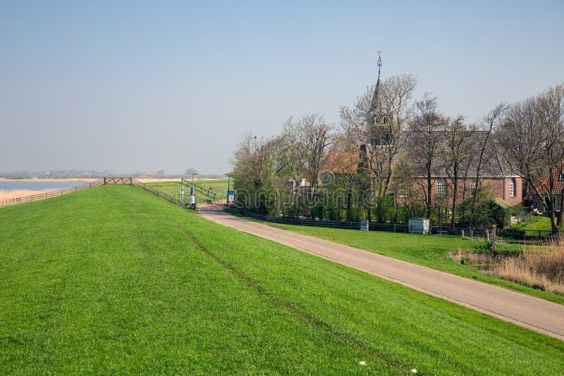 有教会的荷兰村庄Gaast在海保护的水坝后 图库摄影