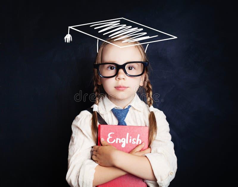 有教育书和毕业帽子的聪明的儿童女学生 库存图片