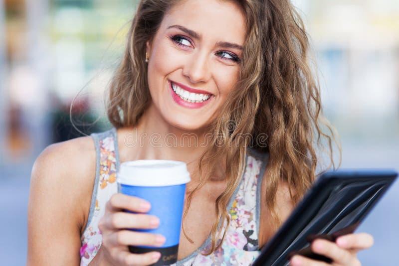 有数字式片剂和咖啡的妇女 库存照片