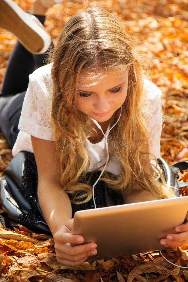 有数字式片剂和耳机的青少年的女孩 免版税库存照片