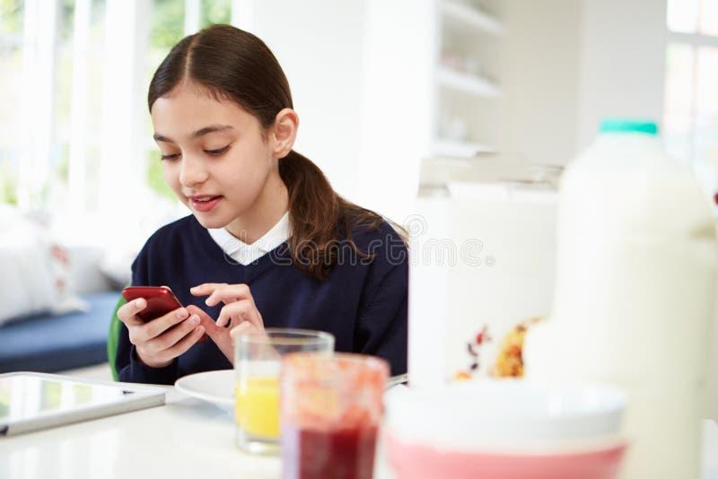有数字式片剂的在早餐的女小学生和机动性 图库摄影