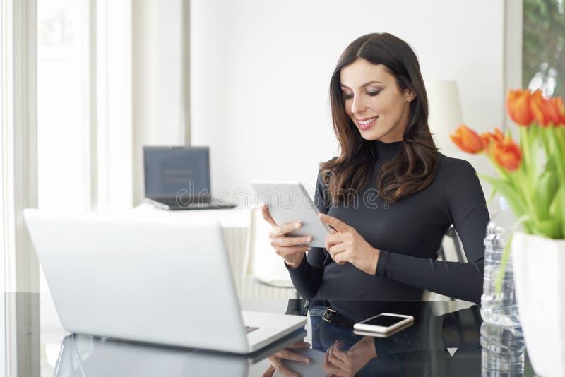 有数字式片剂的妇女在办公室 免版税库存照片