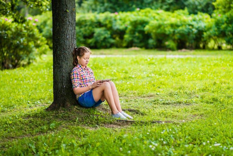 有数字式片剂的少年女孩在她的膝盖在公园在树下 库存照片