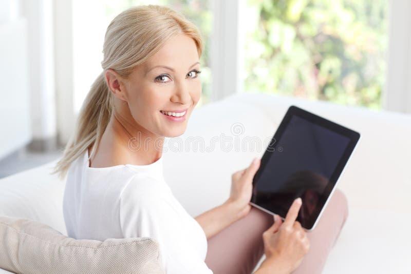 有数字式片剂的微笑的妇女 库存照片