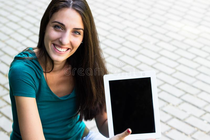 有数字式片剂的愉快的少妇在城市 库存照片