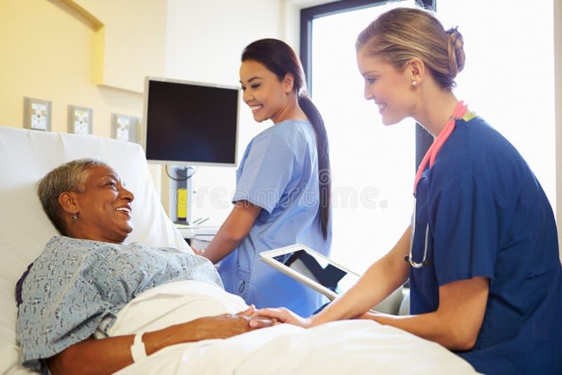 有数字式片剂的护士与妇女在医院病床上谈话 库存照片