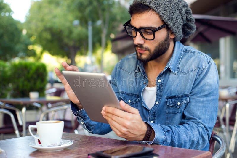有数字式片剂的现代年轻人在街道 免版税库存照片