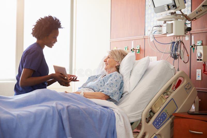 有数字式片剂的医院护士与资深患者谈话 免版税库存照片