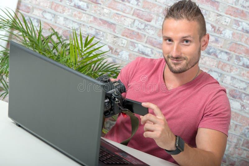 有数字照相机和膝上型计算机的年轻摄影师 免版税库存照片