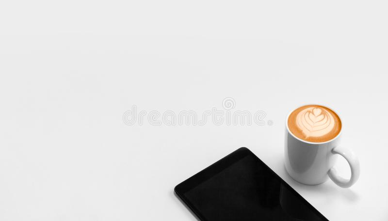 有数字片剂和咖啡热奶咖啡艺术的办公室工作场所与拷贝空间 图库摄影