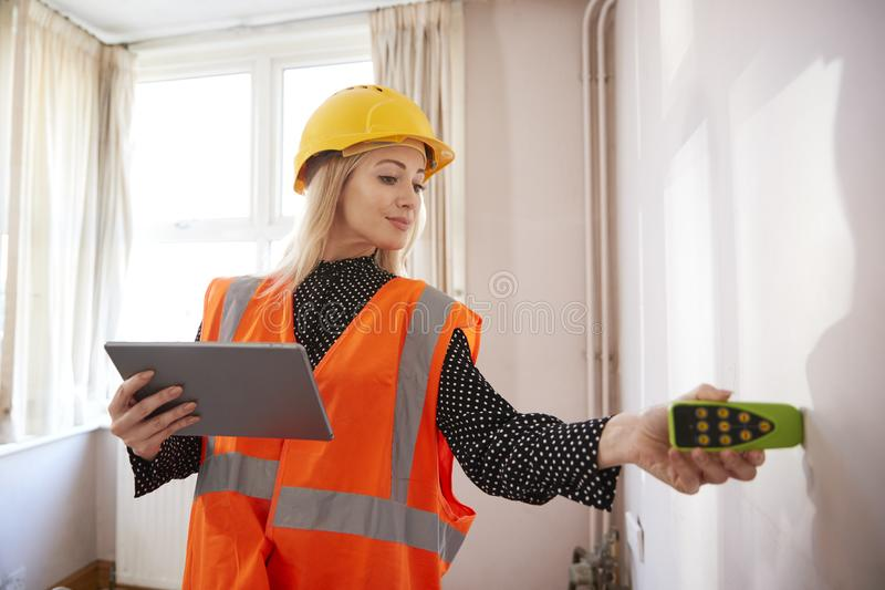 有数字片剂测量的室的女性测量员有激光措施的 免版税库存图片