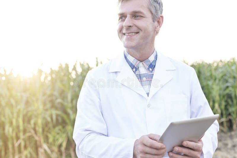 有数字片剂的微笑的成熟科学家在农场 库存图片