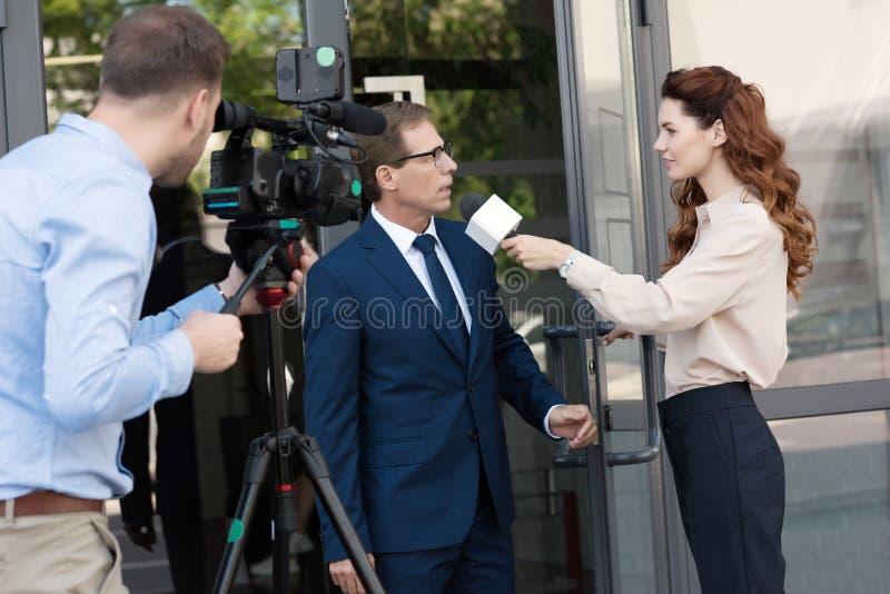 有数码摄像机和专业女主持人采访的商人的摄影师在办公室附近 免版税图库摄影