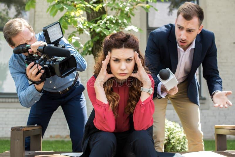 有数码摄像机和男性新闻广播员的摄影师有话筒的谈话与疲乏的女实业家 免版税库存图片