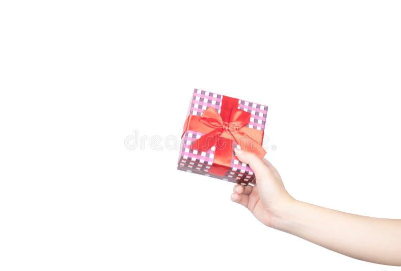 有整洁的修指甲的特写镜头美好和健康妇女手拿着圣诞节礼物盒包裹与红色丝带 免版税库存图片