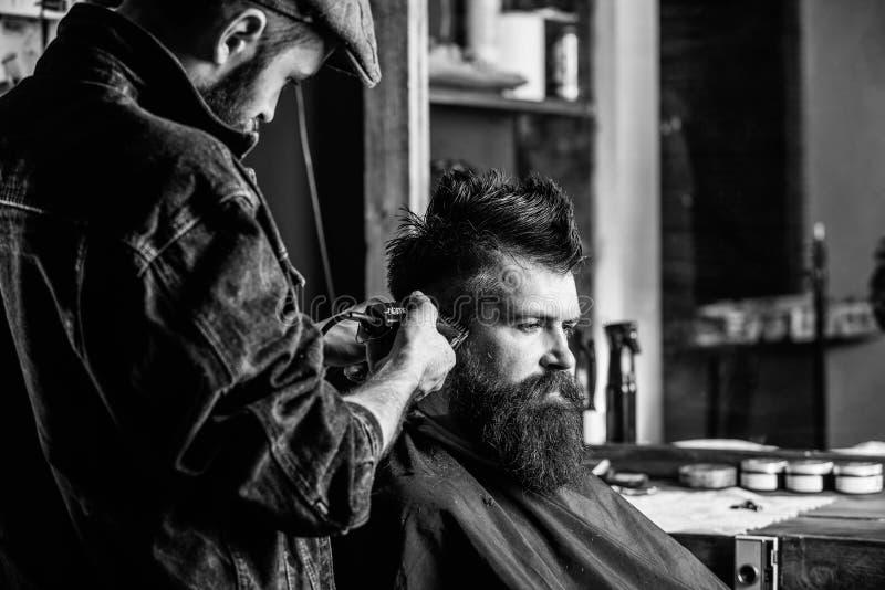 有整理在客户寺庙的飞剪机的理发师头发  得到理发的行家客户 有头发剪刀工作的理发师 库存图片