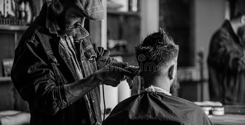 有整理客户,背面图的头发的飞剪机的理发师 得到理发的行家客户 r 图库摄影