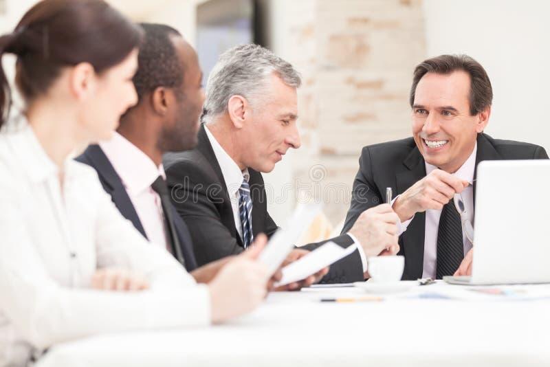 有文书工作的微笑的商人在证券交易经纪人行情室 免版税图库摄影