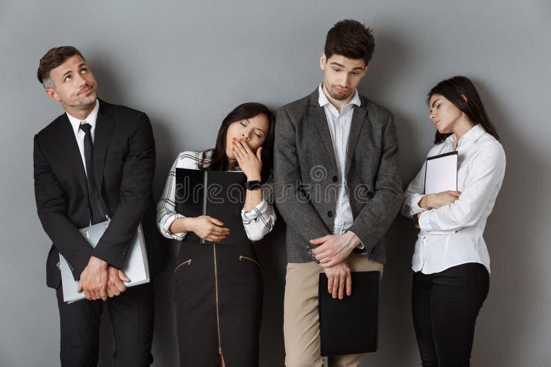 有文件夹和笔记本等待的等候的和疲乏的多文化商人 库存照片