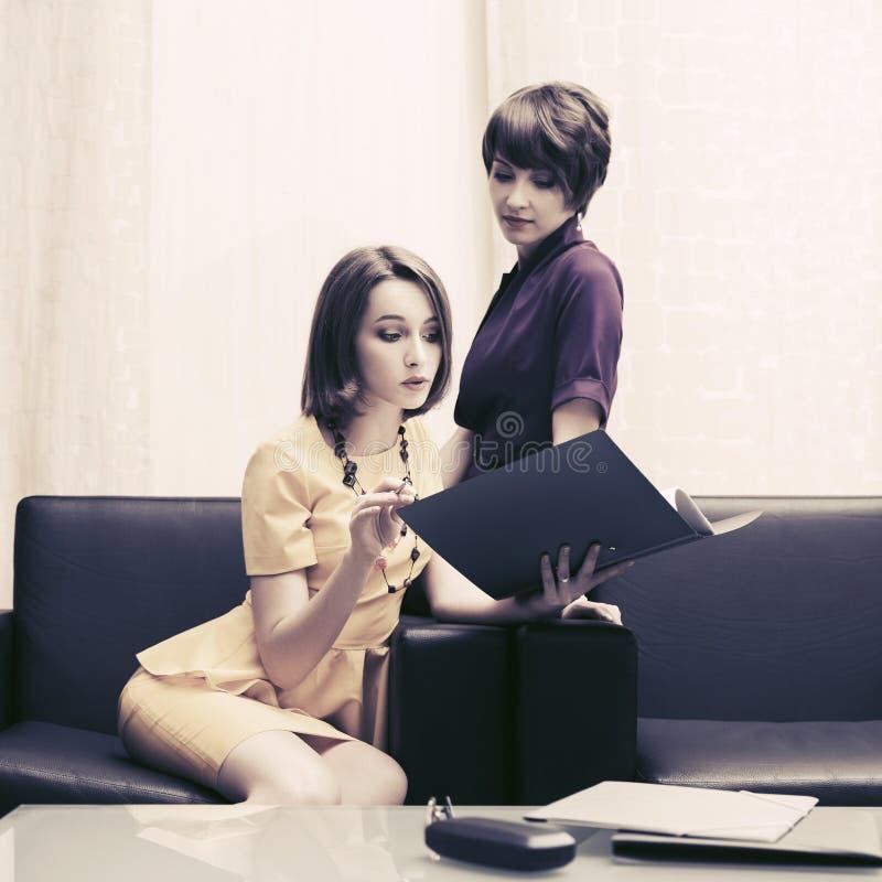 有文件夹的两名年轻时装业妇女在办公室 免版税库存图片