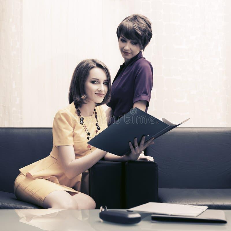 有文件夹的两名年轻时装业妇女在办公室 免版税库存照片