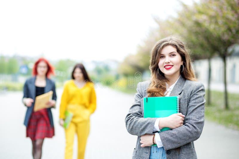 有文件夹的微笑的女生 教育概念、检查、友谊和人 免版税图库摄影