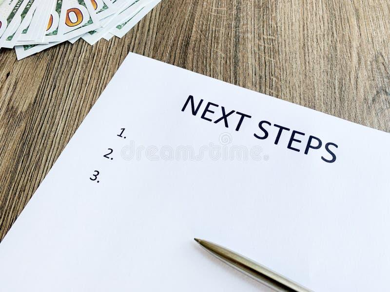 有文本下一个步骤的剪贴板在木书桌上 免版税图库摄影