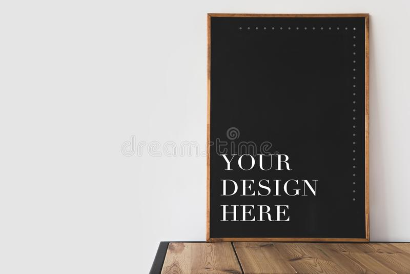 有文本的大黑板您的设计这里在白色的木桌上 库存照片