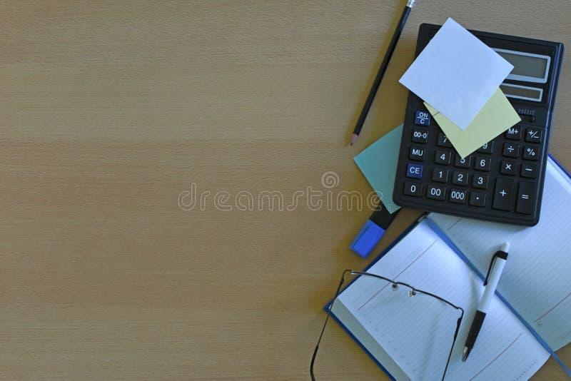 有文本空间的办公室工作场所,与办公用品片剂的木桌,台式计算机和书,顶视图,在光 库存图片