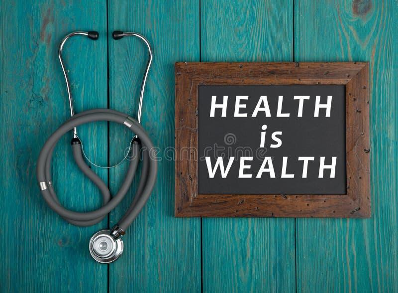 有文本& x22的黑板; 健康是wealth& x22;并且在蓝色木背景的听诊器 免版税库存照片