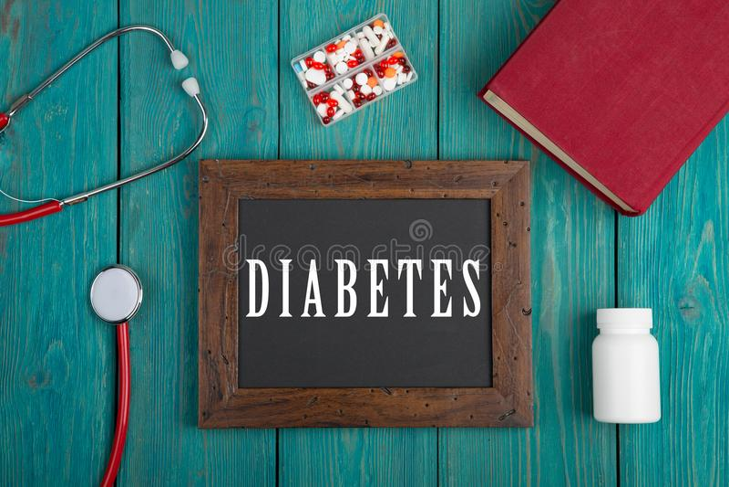 有文本& x22的黑板; Diabetes& x22; 听诊器、药片和书在蓝色木背景 库存照片