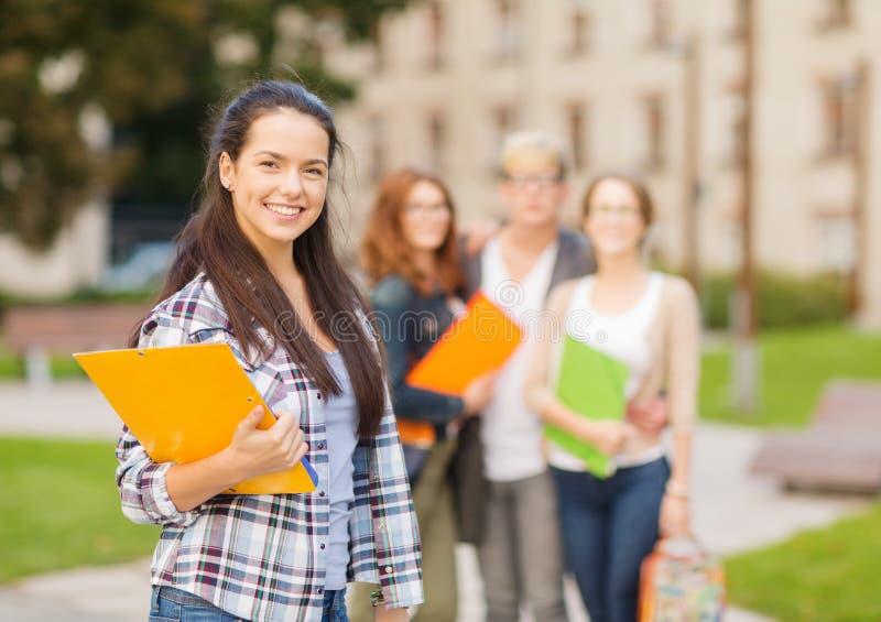 有文件夹的微笑的女学生 库存照片