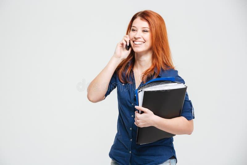 有文件夹的快乐的可爱的少妇谈话在手机 库存图片