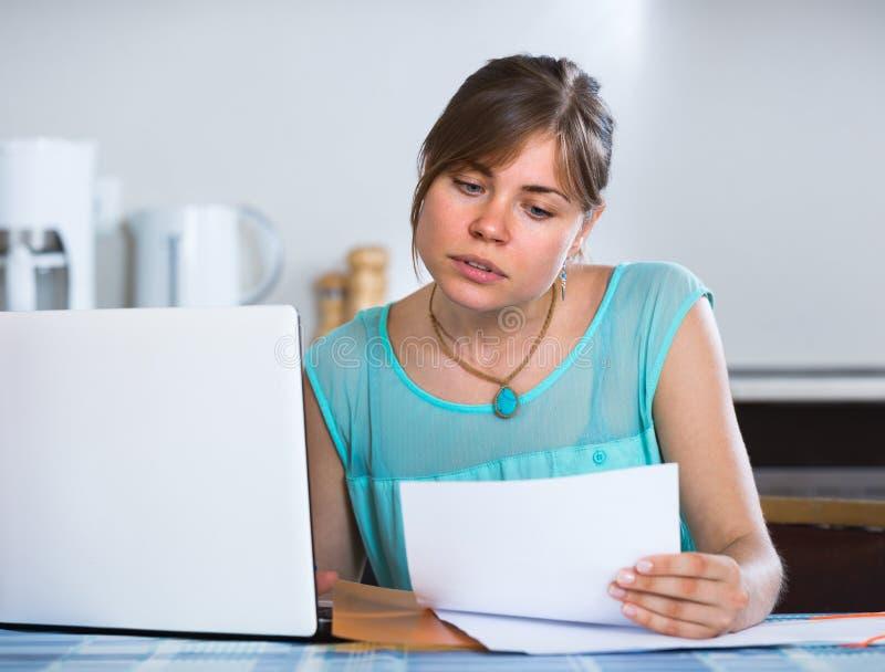 有文件的沮丧的女孩在厨房 免版税库存照片