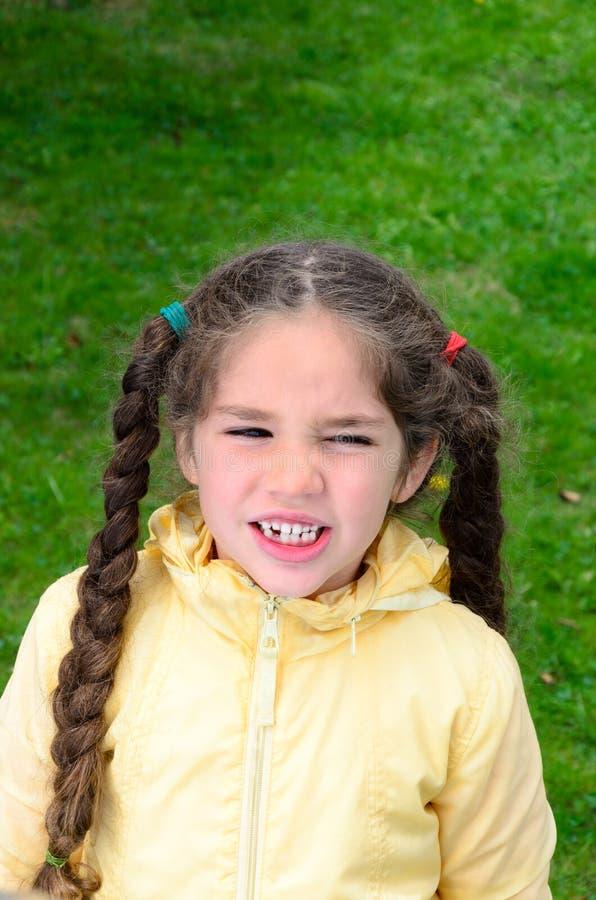 有斜眼看长的辫子的小女孩户外 库存图片