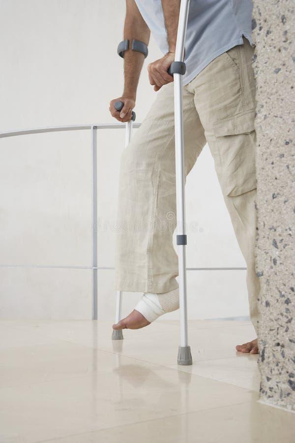 有断腿的人走与拐杖的 库存图片