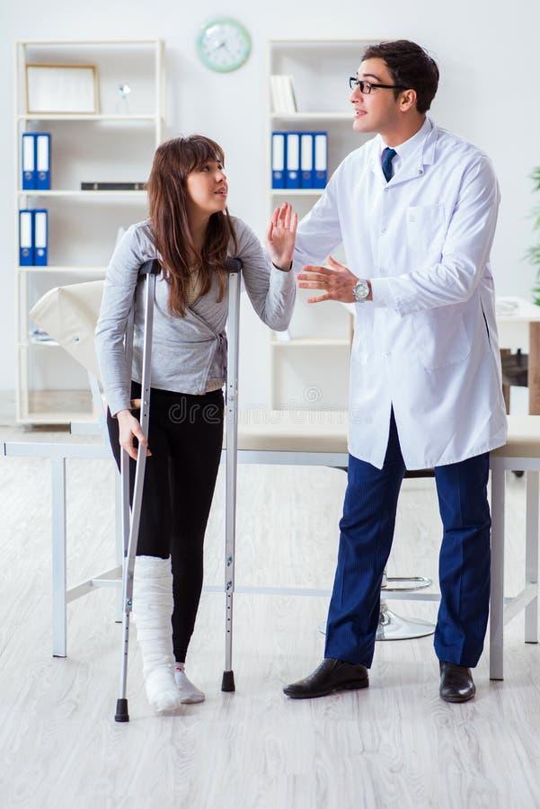 有断腿的医生审查的病人 图库摄影