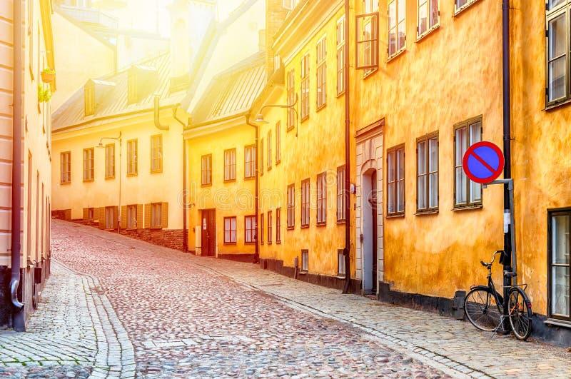 有斯德哥尔摩的Gamla斯坦历史的老中心自行车和黄色中世纪房子的狭窄的鹅卵石街道在夏天 免版税库存图片